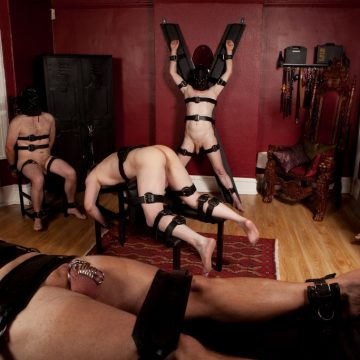 hot scene with multiple slaves restrained and in chastity